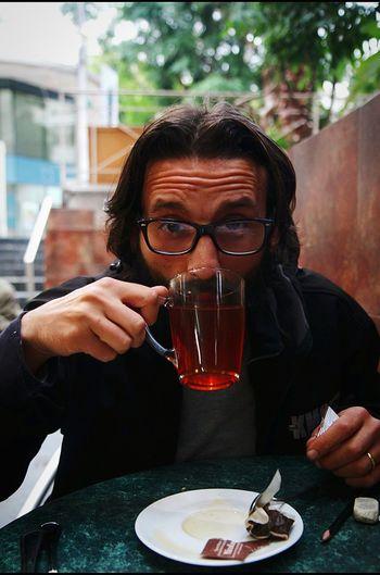 Portrait Of Mature Man Drinking Herbal Tea At Sidewalk Cafe