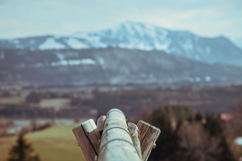 Wooden post against snowcapped mountains
