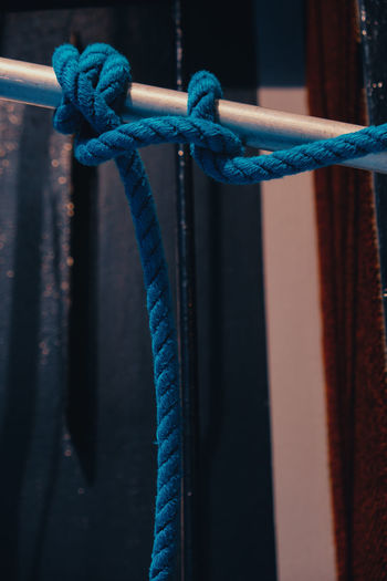 Close-up look to the details of nautical equipment. Blue rope tied up in a knot around a metal stick Tied Up Blue Close-up Rope No People Focus On Foreground Safety Turquoise Colored Nautical Vessel Mode Of Transportation Moored Rope Nautical Equipment Strap Tied Knot Detail Strength Metal Connection Transportation Pattern Red Outdoors Day