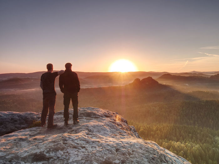 Men standing on mountain against sky during sunset
