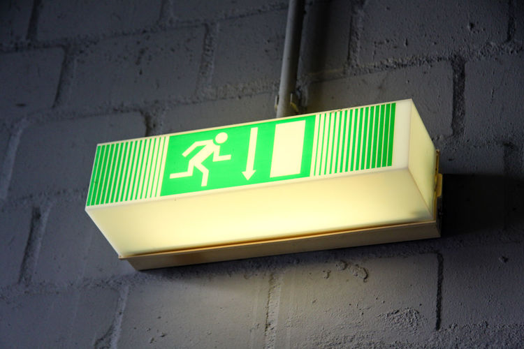 Emergency Exit Bricks Close-up Communication Direction Directional Sign Emergency Exit Exit Green Color Indoor Indoors  Lighted Sign No People Sign Symbol Wall