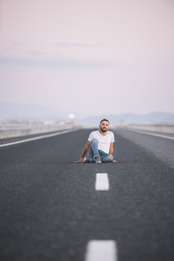 Full Length Portrait Of Man Sitting On Road Against Sky In City