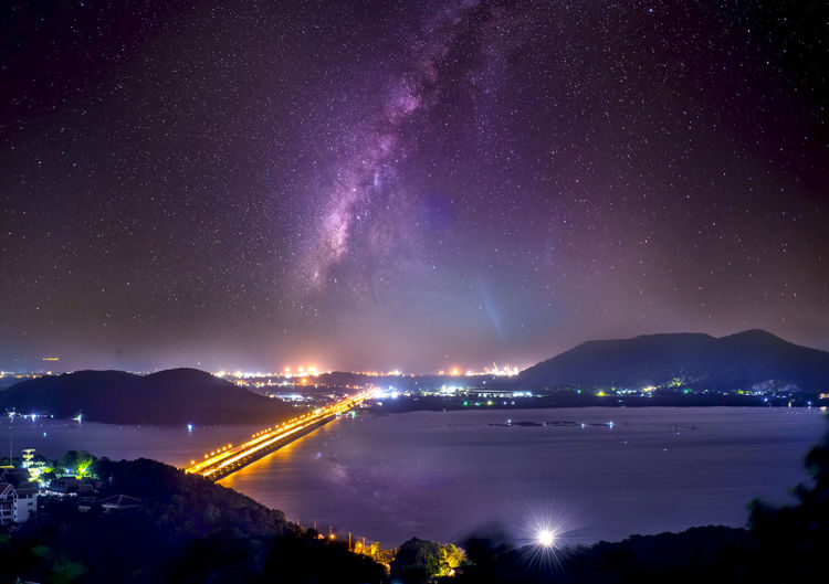 Scenic view of illuminated sea against sky at night