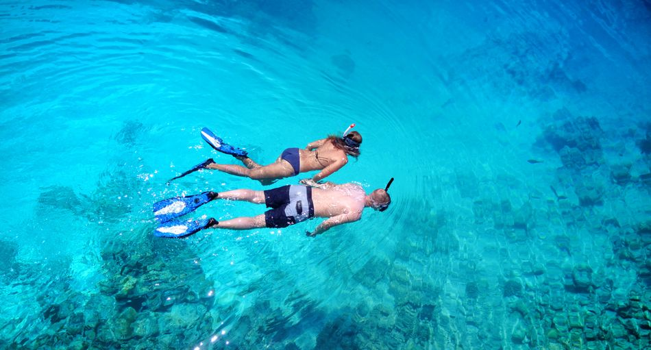 Couple snorkeling over coral reef with drone aerial flying view in crystal clear aqua blue shallow water Snorkeling Couple Top View Coral Reef Romantic Maldives Dive Summer Swimming Honeymoon Crystal Clear Waters Turquoise Water Fun Sea Ocean Happy Relaxing Blue Bird's Eye View Marine
