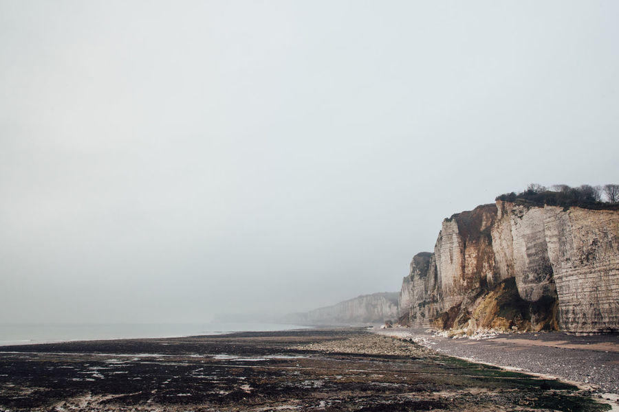 Cliff Landscape Ocean Sea Seascape Beach Tide Low Tide Nature Sky Rock Beauty In Nature Land Tranquility Day Water Scenics - Nature Tranquil Scene Rock - Object Fog Copy Space Rock Formation Solid No People Outdoors Eroded Formation