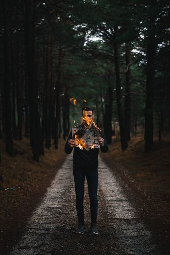 Full length of man holding burning paper while standing on footpath amidst trees