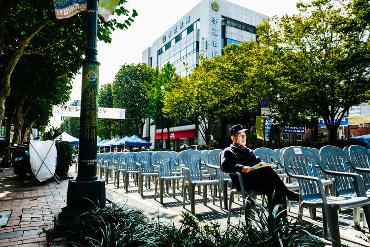 Man sitting on table in city against sky