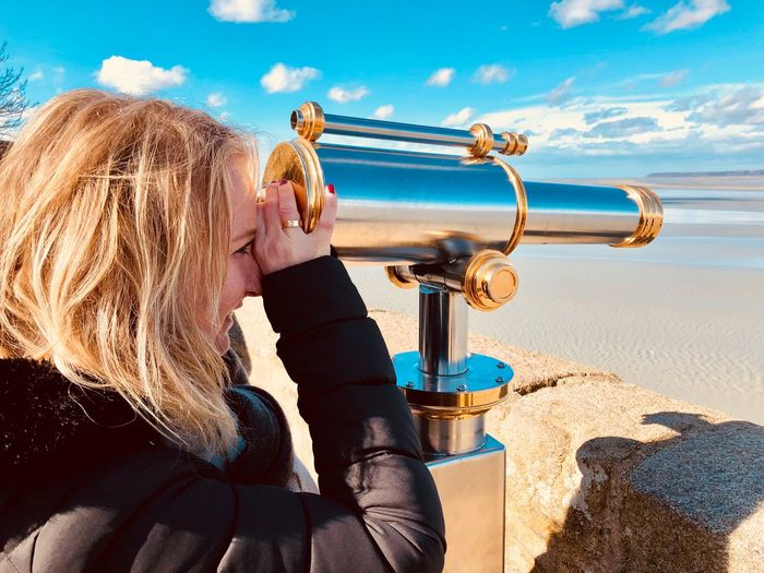 Side view of smiling woman looking through hand-held telescope at beach