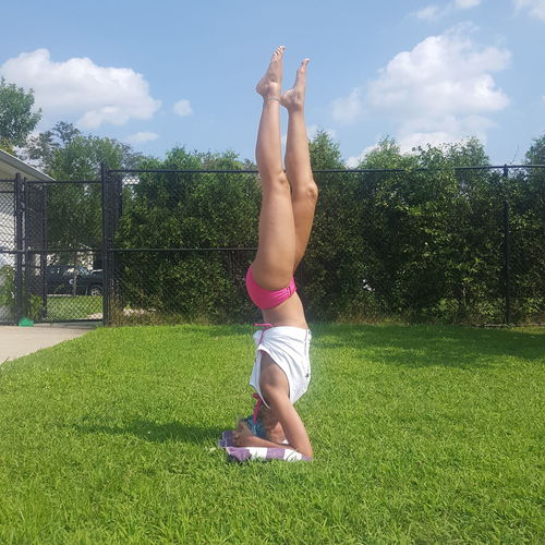 Woman Doing Headstand On Grass