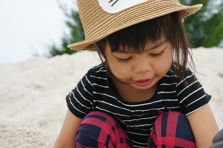 Young girl playing with sand Casual Clothing Child Childhood Clothing Cute Day Focus On Foreground Front View Girls Hat Innocence Land Leisure Activity Lifestyles One Person Outdoors Real People Striped Warm Clothing