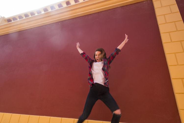 Cheerful woman jumping against maroon wall