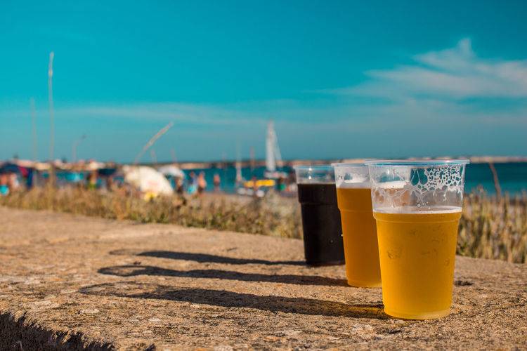 Close-up of glasses of beer on table against sky