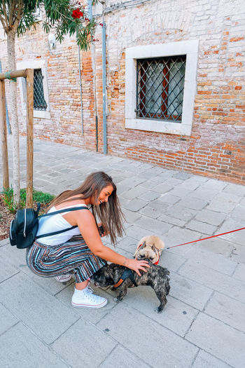young woman petting animal Venice Venice, Italy Italy Travel Travel Destinations Pets Domestic Animals One Animal Domestic Mammal Canine Dog One Person Full Length Women Real People Casual Clothing Young Adult Day Adult Pet Owner Outdoors Happy Petting