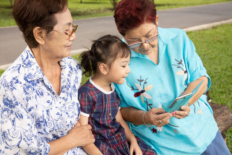 Grandmother showing smart phone to granddaughter at park