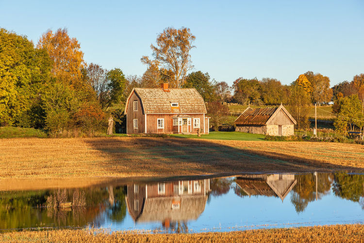 House by lake against sky during autumn