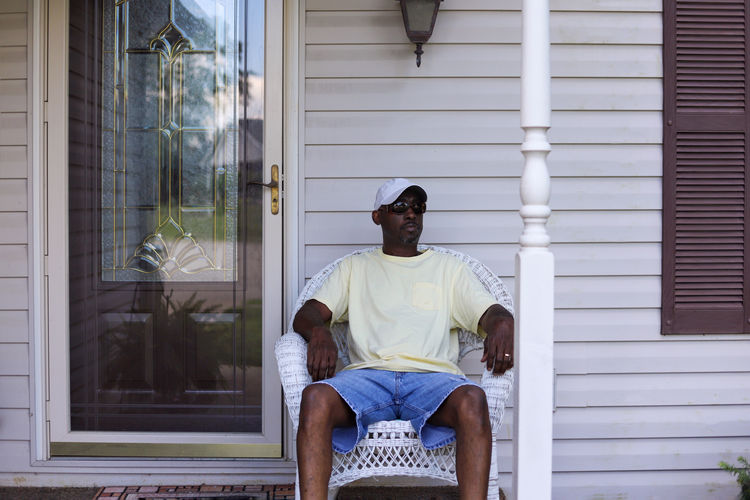 A portrait of an african-american man sitting alone in a wicker chair on a porch