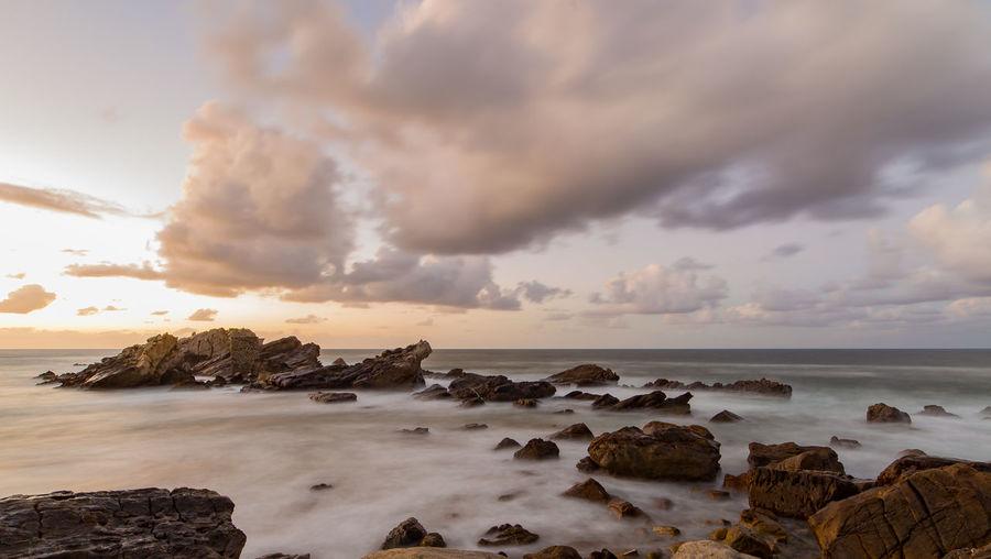 Rocks at sea against sky