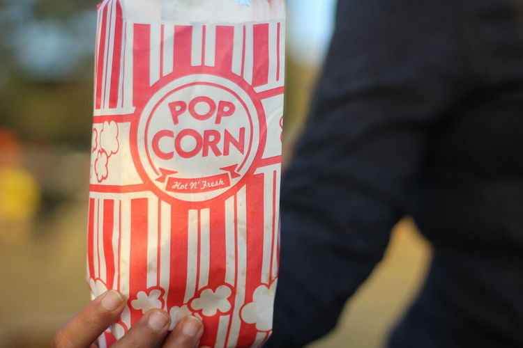 Midsection Of Man Holding Popcorn Bag