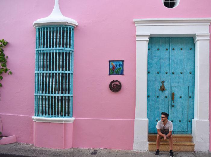 Full length of man sitting against blue door