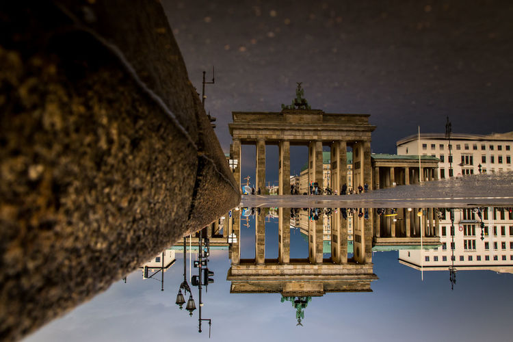 Reflection of brandenburg gate in puddle on street