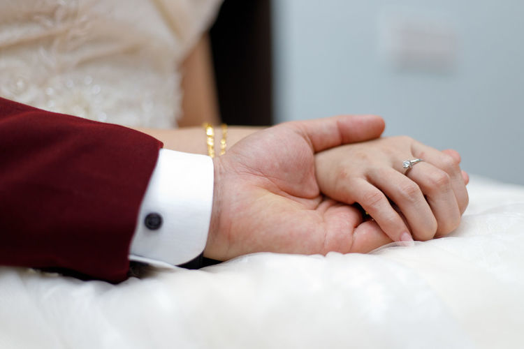 Young married couple holding hands, ceremony wedding day Hand Human Hand Jewelry Human Body Part Ring Adult Women Celebration Close-up Indoors  People Wedding Event Men Midsection Two People Furniture Bed Love Positive Emotion Luxury Finger Togetherness Young Adult Couple