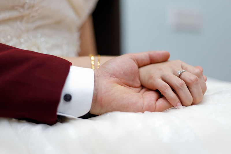 Young married couple holding hands, ceremony wedding day Hand Human Hand Jewelry Human Body Part Ring Adult Women Celebration Close-up Indoors  People Wedding Event Men Midsection Two People Furniture Bed Love Positive Emotion Luxury Finger Togetherness Young Adult Couple #NotYourCliche Love Letter