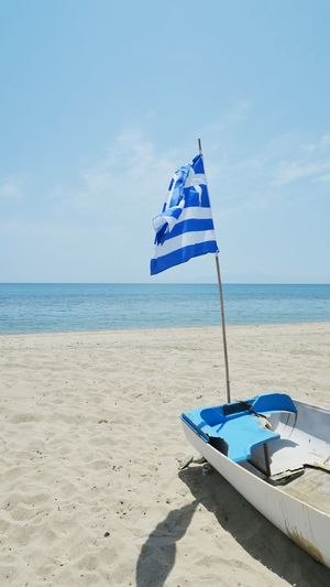 old broken rowing boat with greece flag at the beach of nea plagia, greece Boat Flag Greece Blue Boat Fishing Rowing Boat Beach Sand Horizon Nea Plagia Water Sea Beach Sand Summer Blue Relaxation Flag Sunlight Sky Coastline