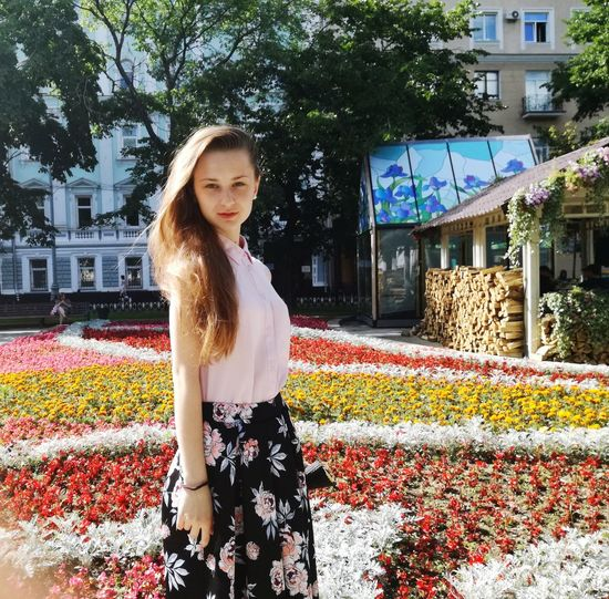 Portrait of confident woman standing against flowers in city