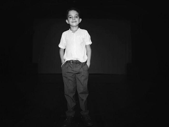 Portrait of girl standing against black background