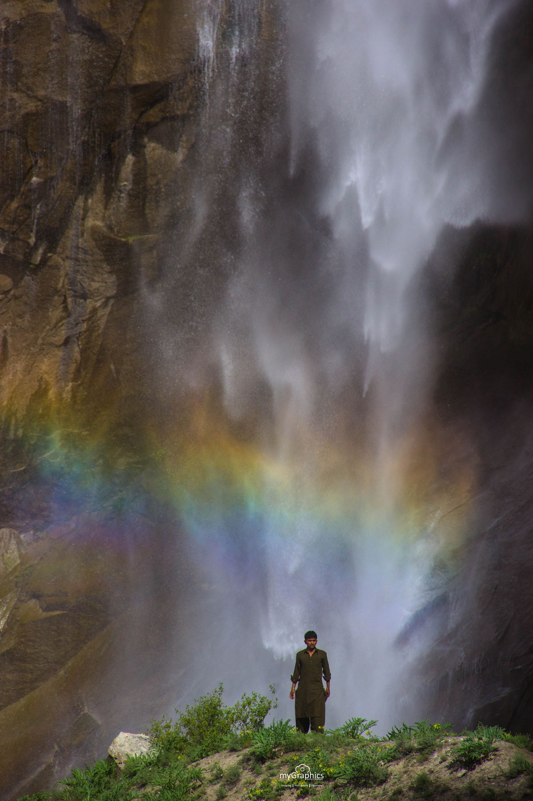 real people, one person, rainbow, silhouette, outdoors, men, rear view, nature, beauty in nature, long exposure, lifestyles, motion, waterfall, leisure activity, scenics, water, day, standing, sky, people