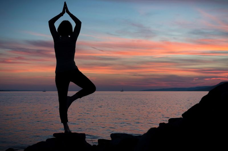 Silhouette woman doing yoga by sea against sky during sunset