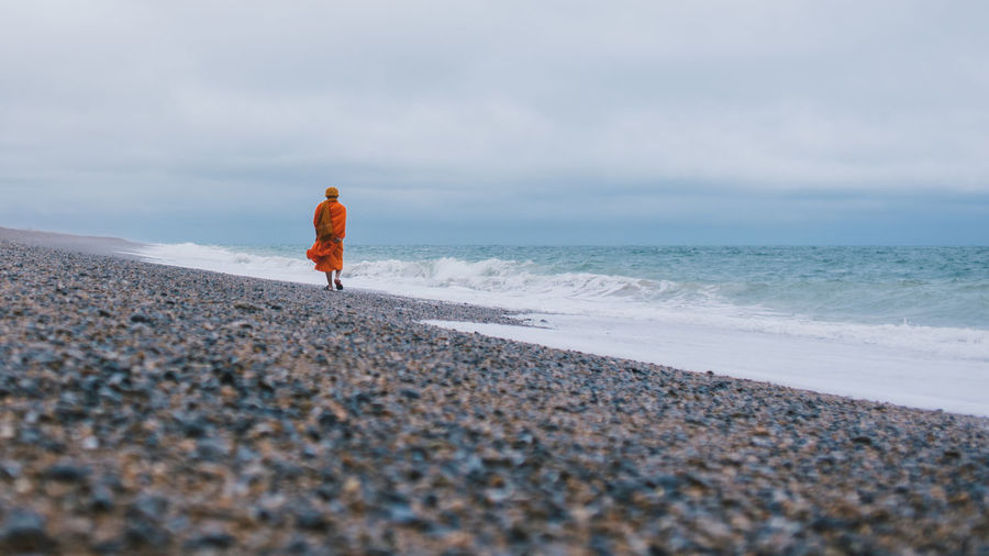 Rear view of monk on beach against sky