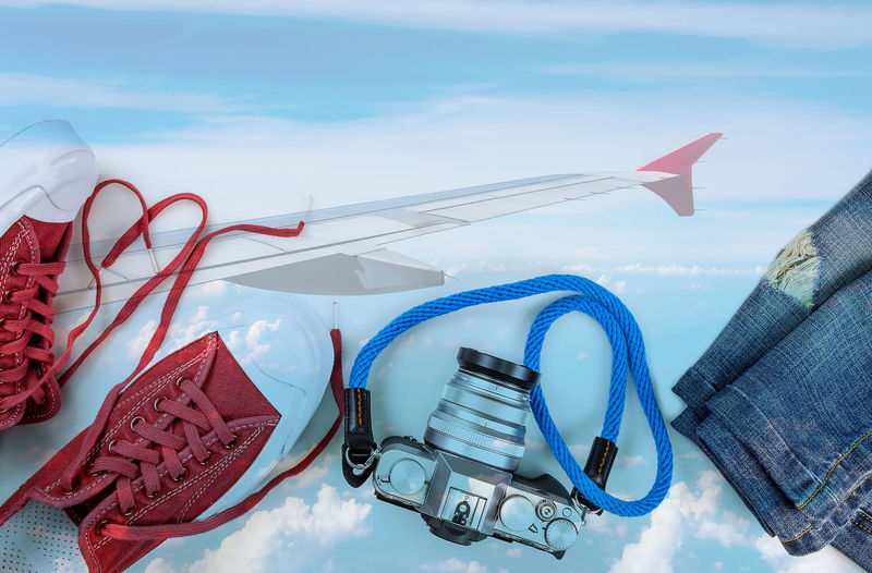 Travel accessories such as camera , sneaker , jean multiply on airplane in the sky picture Cloud Fly Go Jeans Multiply Relaxing Trip Above Accessories Airplane Blue Cemara Close-up Cloud - Sky Day Denim No People Outdoors Shoes Sky Skyscraper Sneaker Travel Destinations