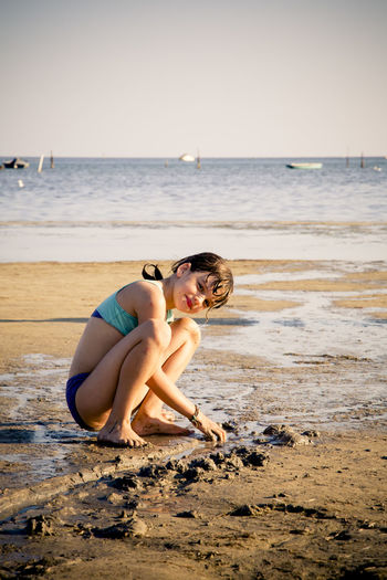 Girl in swimwear playing with sand at beach