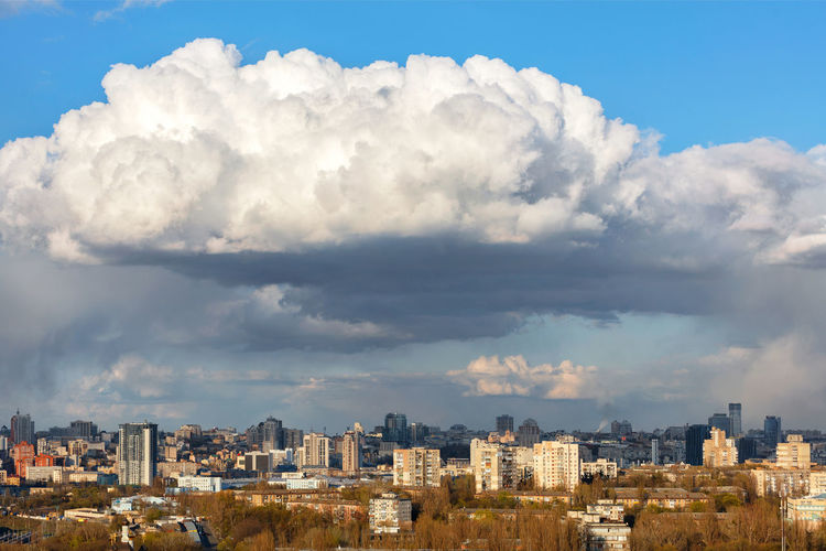 A beautiful spring cityscape with a white cloud hovering over the city in the blue sky.
