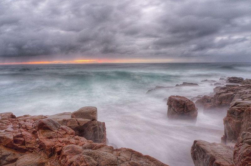 Rocks at sea shore against cloudy sky during sunset