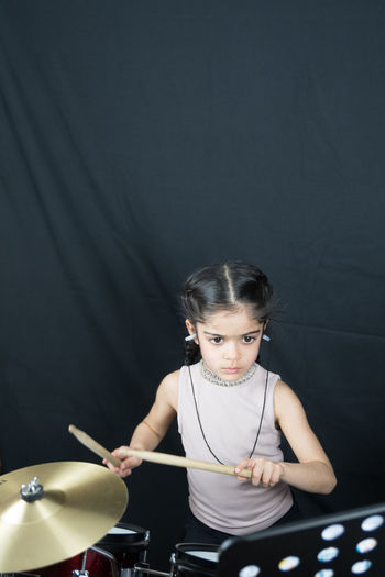 Cute Girl Playing Drum Set Against Black Backdrop