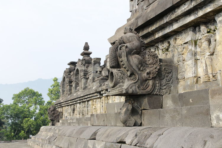Beautiful bas-relief as wall decor carved in stone at Borobudur Temple, Yogyakarta, Indonesia Ancient Ancient Civilization Architecture Art And Craft Building Exterior Built Structure Craft Creativity Day History Human Representation Low Angle View Male Likeness Nature No People Ornate Outdoors Representation Sculpture Sky Statue The Past Travel Destinations