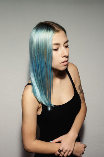 Young woman with dyed hair standing against patterned wall