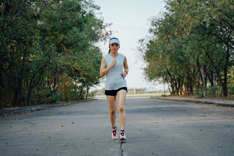 Full length portrait of woman running on footpath