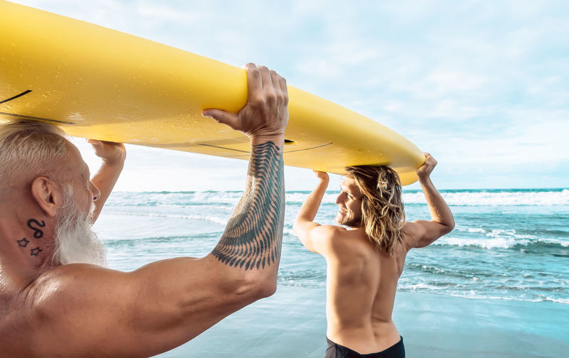 Father and son holding surfboard at beach against sky