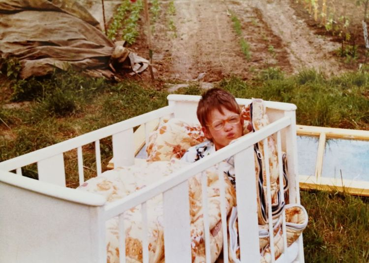 Portrait of boy lying in crib outdoors
