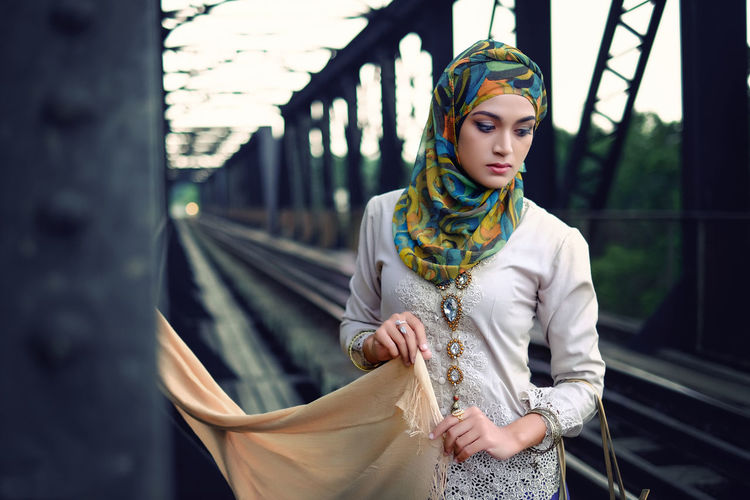Young woman wearing hijab looking down while standing at railway bridge