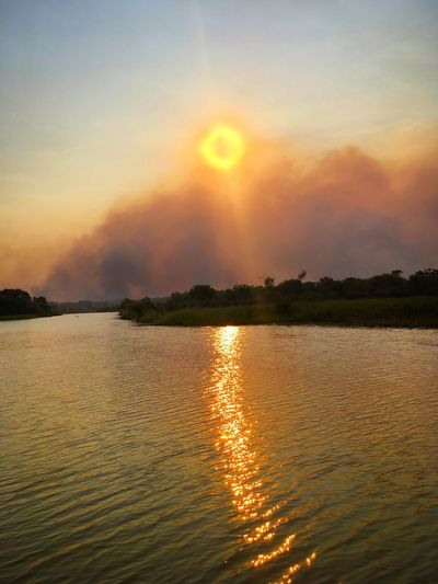 Sunset through the smoke of a bushfire on the banks of Hardie Billabong in the Northern Territory of Australia. Sunset Sun Water Beauty In Nature Scenics Nature Reflection Orange Color No People Sunlight Outdoors Hardie Billabong Northern Territory Australia Global Warming Apocalypse The Great Outdoors - 2017 EyeEm Awards