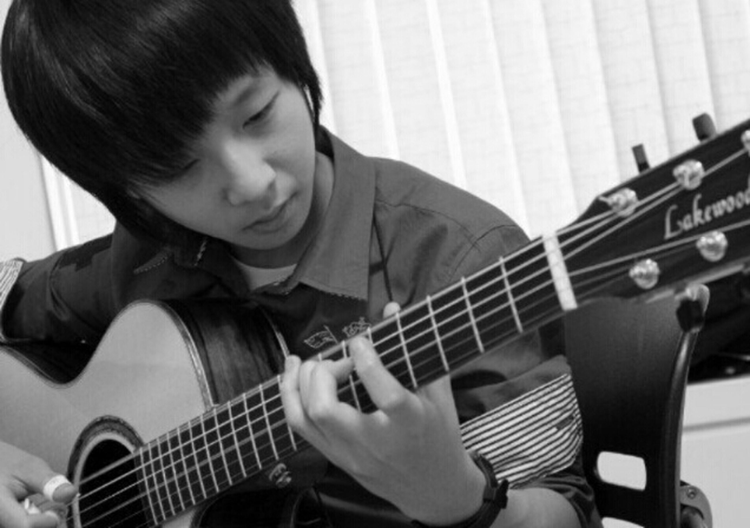 lifestyles, casual clothing, leisure activity, indoors, person, holding, music, musical instrument, sitting, arts culture and entertainment, childhood, playing, occupation, guitar, side view, three quarter length, boys, waist up