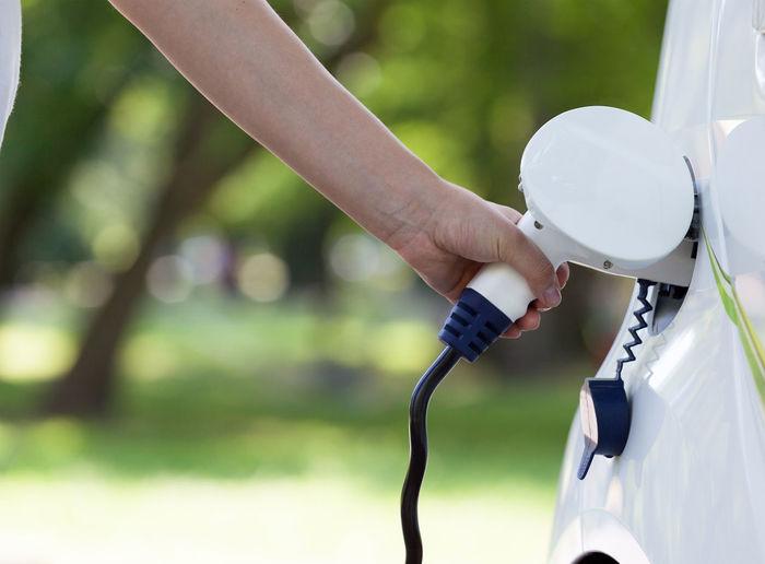 Cropped hand charging car at station