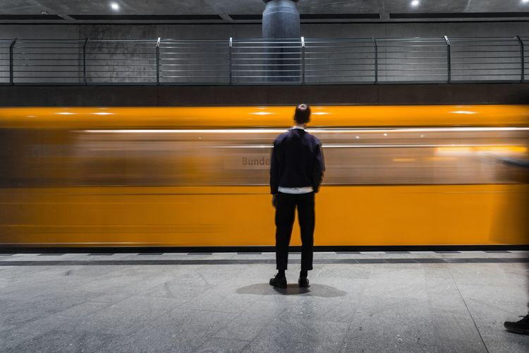 Rear view of man standing against train at subway station