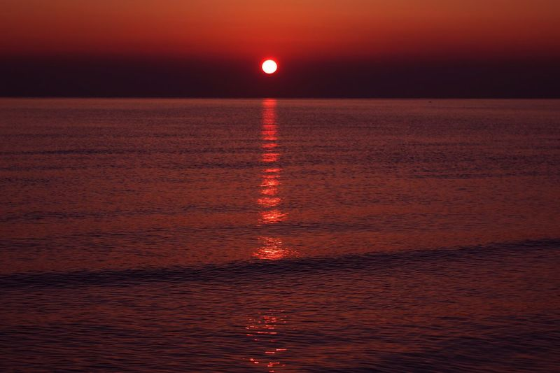 Sunrise Travel Travel Destinations Water Beauty In Nature Sky Sea Scenics - Nature Sunset Nature Tranquility Reflection Outdoors Tranquil Scene No People Idyllic Non-urban Scene Horizon Over Water Orange Color Land Nightlife Red Horizon
