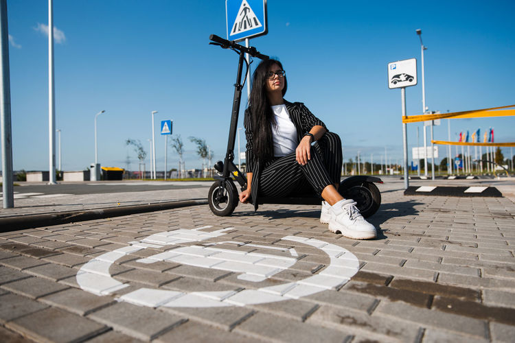 Woman with push scooter sitting on footpath against blue sky