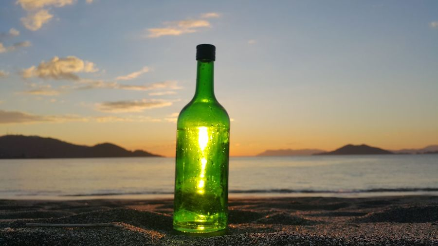 Close-up of bottle on shore at beach against sky during sunset